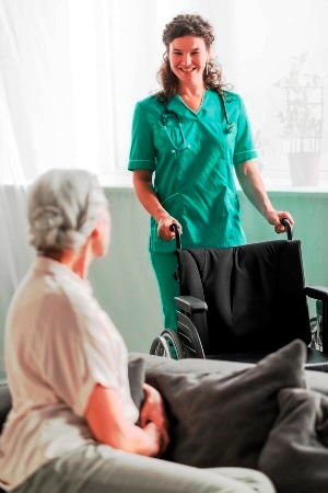 Foley Alabama CNA holding wheelchair for senior patient